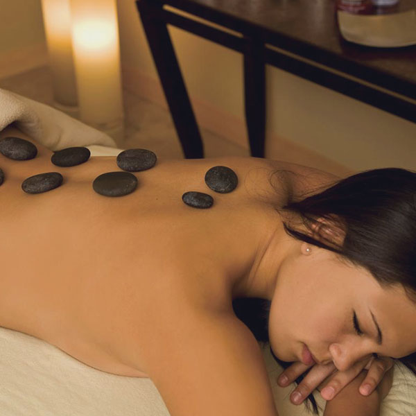 woman with hot stones on back during massage