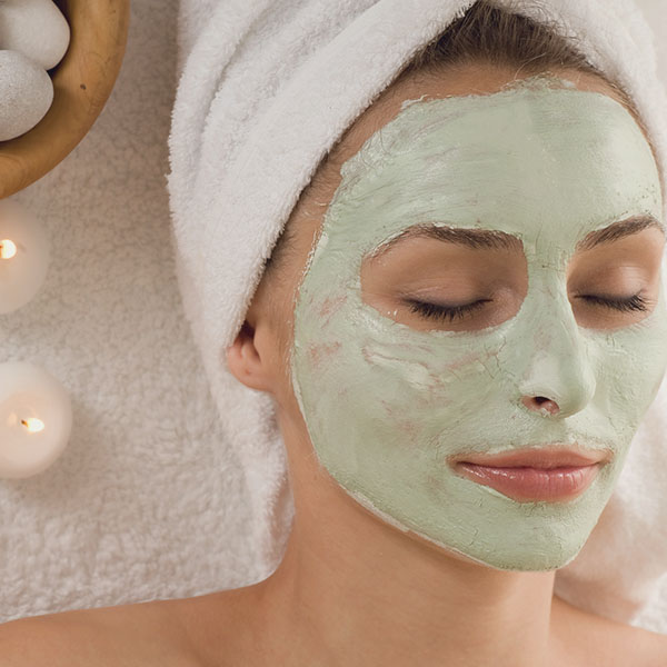 woman with green face mask at spa