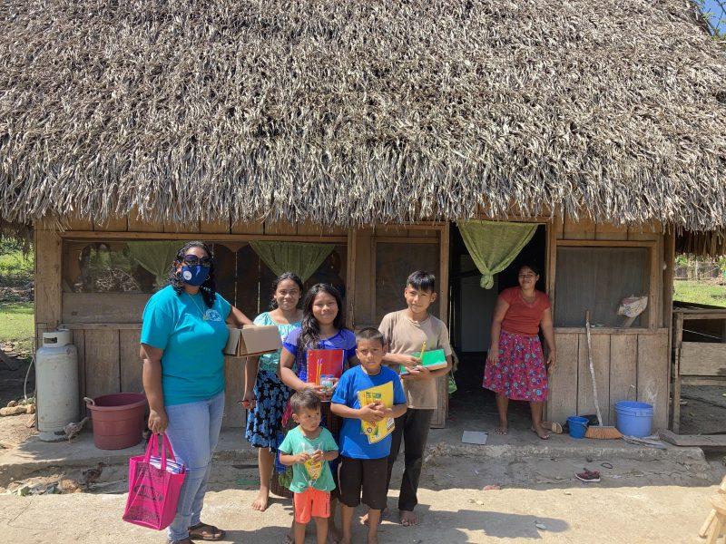 Valerie distributing school supplies to local school children